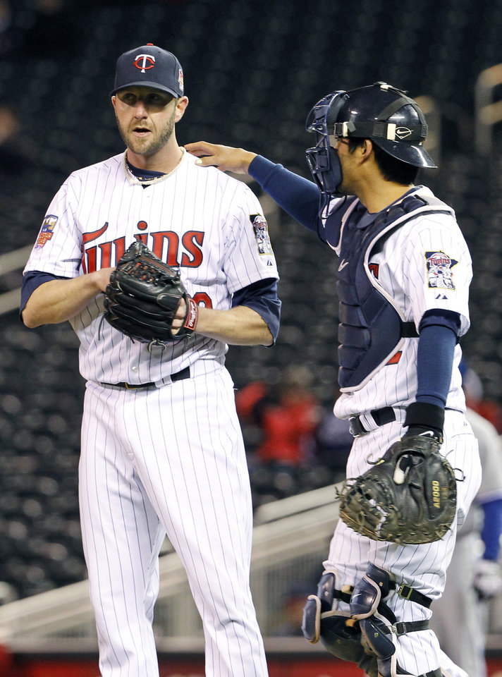 Photo - Minnesota Twins catcher Kurt Suzuki, right, encourages relief pitcher Jared Burton, left, after Burton walked Toronto Blue Jays' Moises Sierra to load the bases during the ninth inning of a baseball game in Minneapolis, Tuesday, April 15, 2014. The Blue Jays won 9-3. (AP Photo/Ann Heisenfelt)