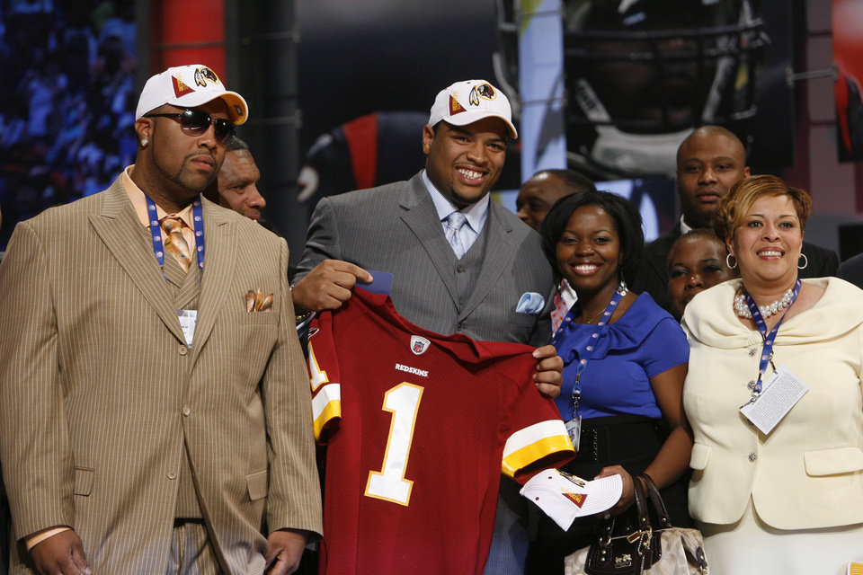 Photo - Oklahoma offensive tackle Trent Williams holds up a jersey with family and friends after he was selected as the fourth overall pick by the Washington Redskins in the first round of the NFL Draft at Radio City Music Hall Thursday, April 22, 2010, in New York. (AP Photo/Jason DeCrow)