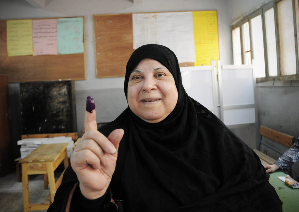 Photo -   An Egyptian woman shows her inked finger after casting her vote inside a polling station, in Giza, Egypt, Wednesday, May 23, 2012. More than 15 months after autocratic leader Hosni Mubarak's ouster, Egyptians streamed to polling stations Wednesday to freely choose a president for the first time in generations. (AP Photo/Mohammed Asad)