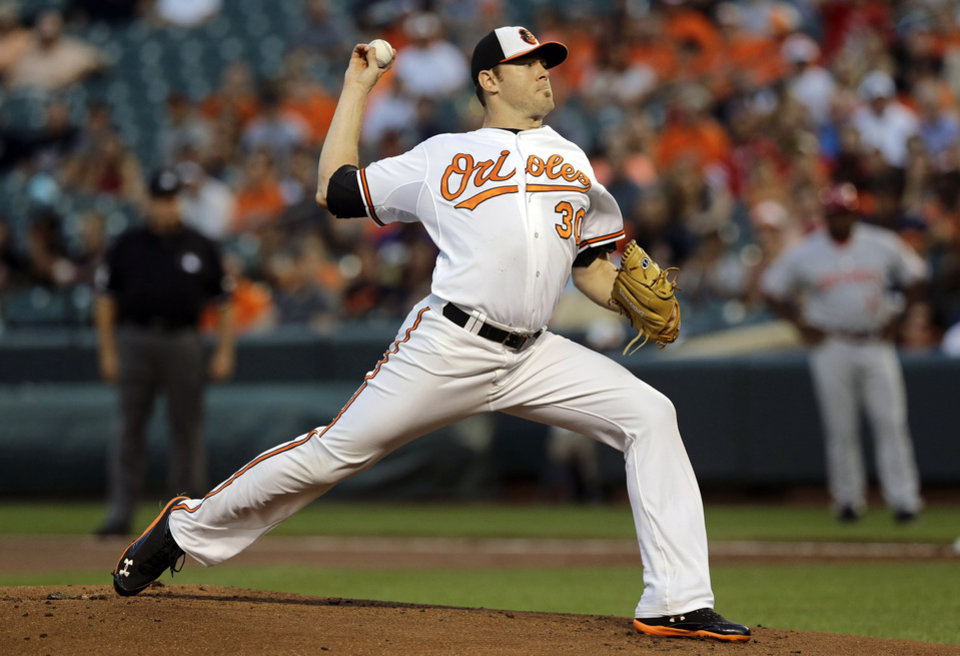 Photo - Baltimore Orioles starting pitcher Chris Tillman throws to the Cincinnati Reds in the first inning of an interleague baseball game, Thursday, Sept. 4, 2014, in Baltimore. (AP Photo/Patrick Semansky)