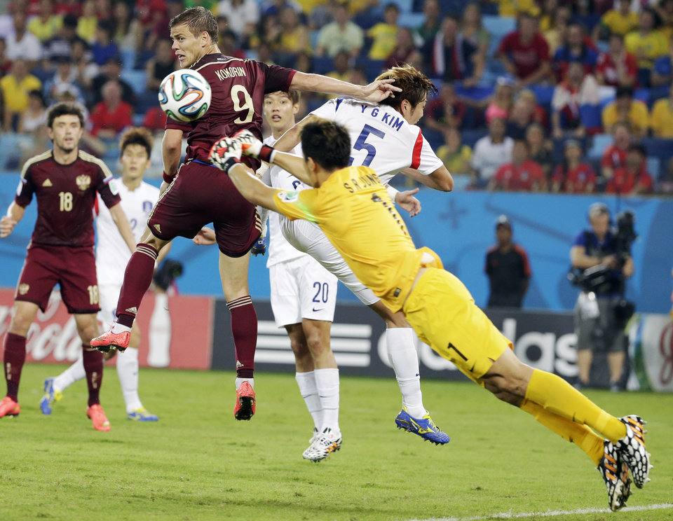 Photo - South Korea's goalkeeper Jung Sung-ryong punches the ball away from Russia's Alexander Kokorin and South Korea's Kim Young-gwon during the group H World Cup soccer match between Russia and South Korea at the Arena Pantanal in Cuiaba, Brazil, Tuesday, June 17, 2014.  (AP Photo/Felipe Dana)