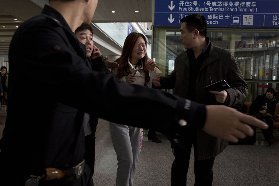 Photo - A woman cries at the arrival hall of the International Airport in Beijing, China, Saturday, March 8, 2014. Relatives and friends were arriving at Beijing airport for news after a Malaysia Airlines Boeing 777-200 was reported missing on a flight from Kuala Lumpur to Beijing Saturday. (AP Photo/Ng Han Guan)