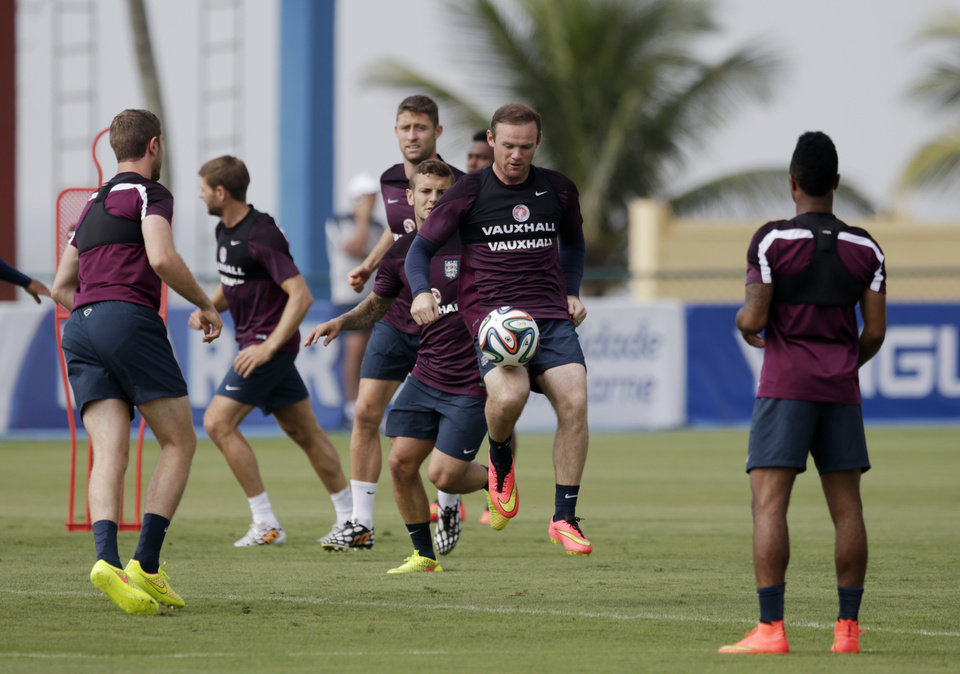 Photo - England national soccer team player Wayne Rooney, center, controls a ball during a squad training session for the 2014 soccer World Cup at the Urca military base in Rio de Janeiro, Brazil, Wednesday, June 11, 2014.  The England soccer team are staying in Rio de Janeiro as their base city for the 2014 soccer World Cup.  (AP Photo/Matt Dunham)