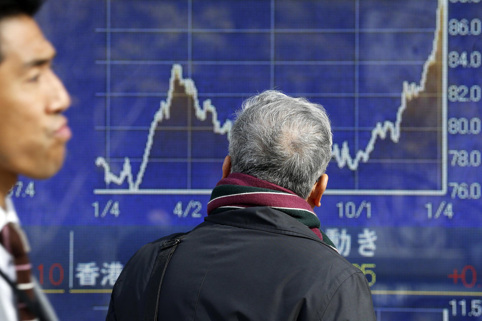 A man looks at an electronic stock board of a securities firm in Tokyo, Thursday, Jan. 10, 2013. A positive start to U.S. corporate earnings season helped boost Asian stock markets Thursday. (AP Photo/Koji Sasahara)