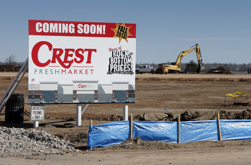 "Photo - A ""coming soon"" sign and construction vehicles mark the site of a future Crest Fresh Market in Norman. The store, in the University Town Center shopping center, is expected to open in October.  Photo by STEVE SISNEY, THE OKLAHOMAN"