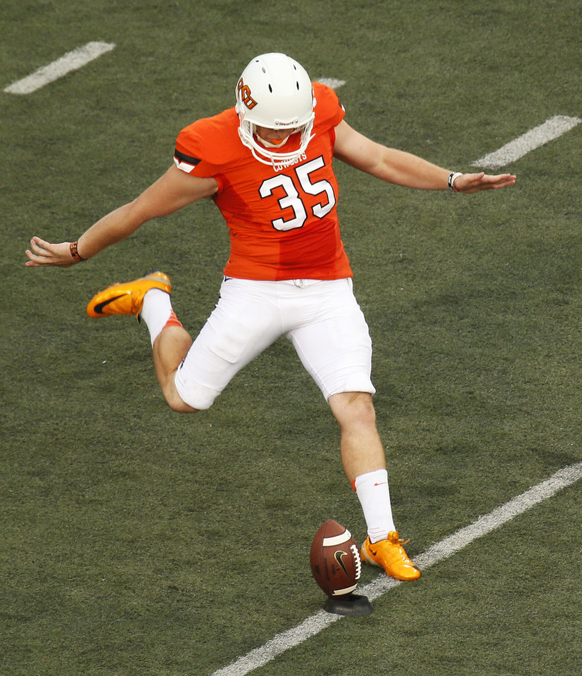 Photo - Oklahoma State's Kip Smith (35) kicks off during a college football game between the Oklahoma State University Cowboys (OSU) and the Lamar University Cardinals at Boone Pickens Stadium in Stillwater, Okla., Saturday, Sept. 14, 2013. Photo by Nate Billings, The Oklahoman