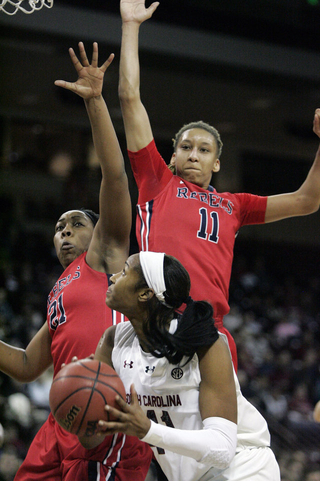 Photo - South Carolina's Alaina Coates (41) looks to take her shot as Ole Miss's Shequila Joseph (21) and Kenyatta Jenkins (11) try to defend  during the first half of an NCAA college basketball game Thursday, Jan. 30, 2014, in Columbia, S.C. (AP Photo/Mary Ann Chastain)