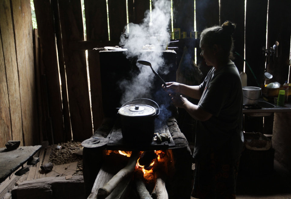 In this Nov. 14, 2012 photo, Lidia Romero cooks in her home in the Carro Cue settlement near Curuguaty, Paraguay. Romero's son De Los Santos was killed and their daughter Lucia was imprisoned during the �Massacre of Curuguaty� on June 15 when negotiations between farmers occupying a rich politician's land ended with a barrage of bullets that killed 11 farmers and 6 police officers. For Romero, the fight for a plot of farm land drew much too high a price. �With my daughter in jail and my son dead, I am destroyed,� she said. �I barely have the will to keep on living.�  (AP Photo/Jorge Saenz)