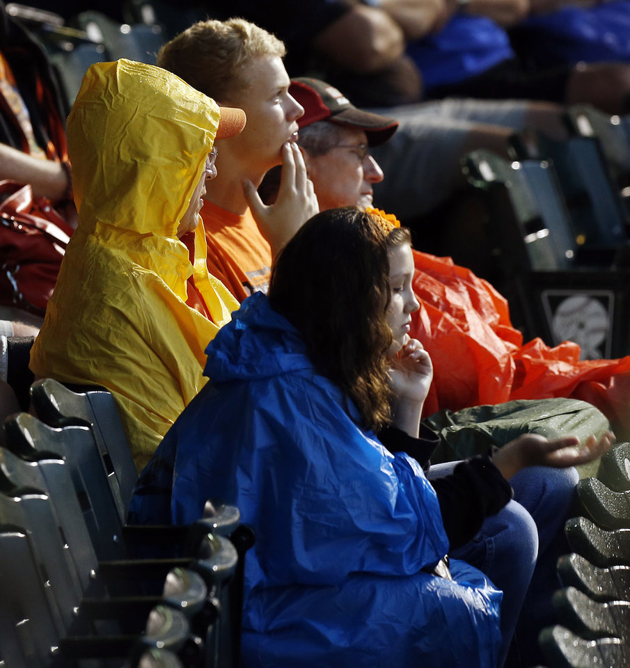 Photo - Fans sit in the stands during a rain delay before the Bedlam college baseball game between Oklahoma and Oklahoma State in the Big 12 baseball tournament at the Chickasaw Bricktown Ballpark in Oklahoma City,  Friday, May 23, 2014. Photo by Nate Billings, The Oklahoman