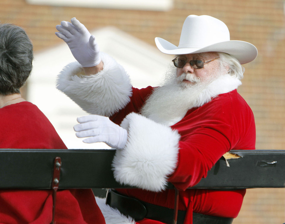 Santa waves to children Saturday during Stockyards City�s annual Cowboy Christmas parade.