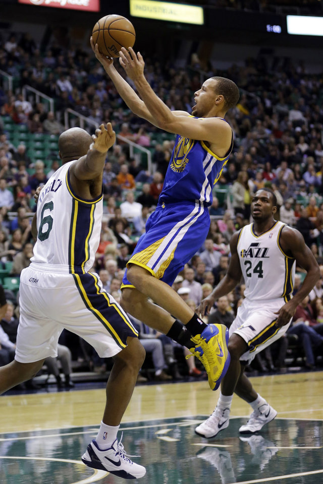Photo - Golden State Warriors guard Stephen Curry, center, lays the ball up as Utah Jazz point guard Jamaal Tinsley (6) defends and forward Paul Millsap (24) watches in the first quarter of an NBA basketball game, Wednesday, Dec. 26, 2012, in Salt Lake City. (AP Photo/Rick Bowmer)