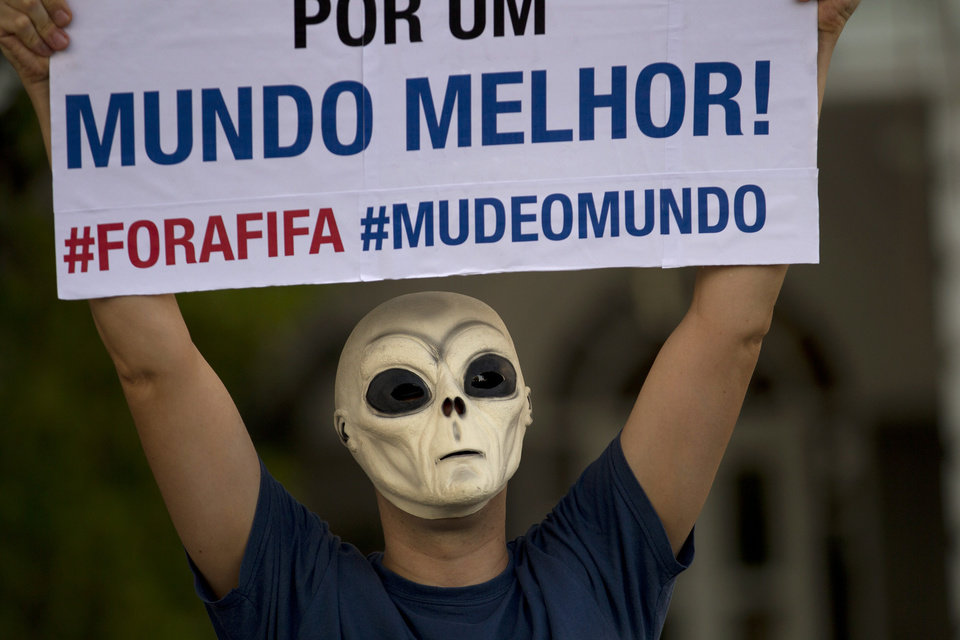 Photo - A man wearing an ET mask holds a sign that reads in Portuguese