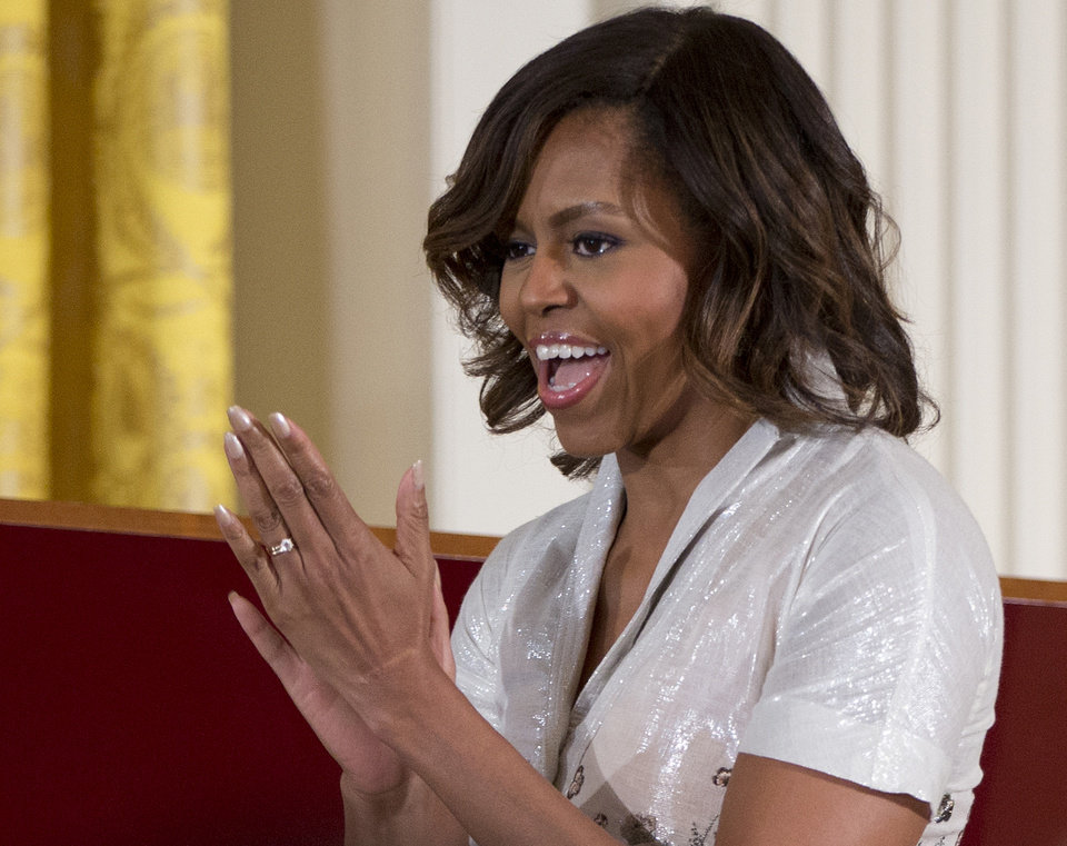 Photo - FILE - This May 12, 2014 file photo shows first lady Michelle Obama applauding as she and Jill Biden, wife of Vice President Joe Biden, hosted their annual Mother's Day tea to honor military mothers, in the East Room of the White House in Washington. Count on singing and dancing, maybe even a few magic tricks, when the curtain goes up Tuesday on the very first White House talent show. Michelle Obama and the President's Committee on the Arts and the Humanities are the hosts for the show, featuring acts by students from poor-performing schools that participate in the committee's Turnaround Arts program. Several major artists, including actress Sarah Jessica Parker, are slated to perform. (AP Photo/Carolyn Kaster, File)