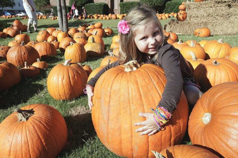 Photo - Kinsley Pulido, 4, hugs a pumpkin in the pumpkin patch at Southern Hills Christian Church in Edmond Tuesday, Sept. 28. 2010. Photo by Paul B. Southerland, The Oklahoman ORG XMIT: KOD