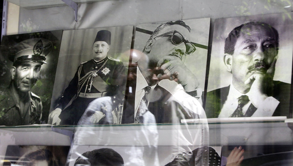 Photo -   Egyptians are reflected in pictures showing late Egyptian presidents Mohammed Naguib, left, Gamal Abdel Nasser, second right, Anwar Sadat, right, and Egypt's last King Farouk, second left, at a photo shop in Cairo, Egypt, Tuesday, May 22, 2012. The May 23-24 presidential election is the first since last year's ouster of longtime authoritarian ruler Hosni Mubarak, marking the first time Egyptians will choose their leader in a race overseen by international monitors. (AP Photo/Amr Nabil)