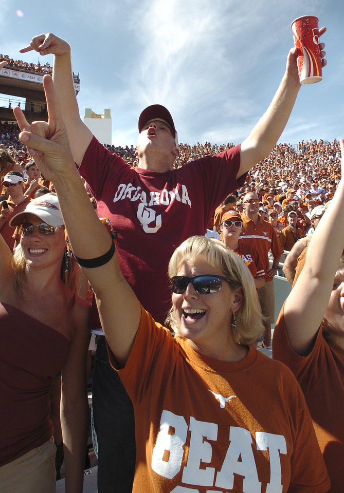 Photo - Oklahoma fan Andy Slania, of Houston sits among Texas fans, including Dee Dahlstrom, of San Antonio, foreground, as they both cheer for their favorite teams as they begin the game during the University of Oklahoma Sooners (OU) college football game against the University of Texas (UT), in the Red River Shootout at the Cotton Bowl, on Saturday, Oct. 7, 2006, in Dallas, Texas,     by Bill Waugh, The Oklahoman  ORG XMIT: KOD