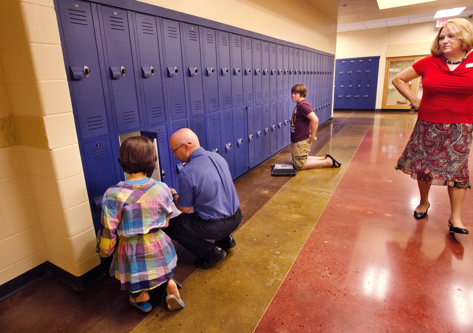 Photo - Assistant Principal Danny Clifton, second from left, helps a student with her locker combination as another student waits for assistance at his locker. At right is Principal JeanAnn Gaona.  About 600 students  and their teachers inaugurated the newest school in the Choctaw/Nicoma Park School District when they started classes for this academic year Tuesday morning, August 23, 2011, at Choctaw Middle School.   The 110,000 square foot building replaces a school that has served the school district since the 1930s.  Photo by Jim Beckel, The Oklahoman