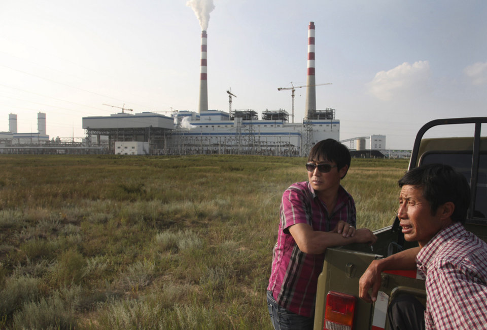 """Photo - In this Wednesday, Aug. 6, 2014 photo, farmers Adiya, left, and Baiyunde, right, stand in front of a state-of-the-art power plant that turns millions of tons of coal every year into methane in northern China's Inner Mongolia province.  As a boy growing up there, Adiya could ride his horse through waist-high grass for miles without meeting another person. Now, the 32-year-old says he stays indoors some mornings because of the industrial stench. Since the plant started running in December, it has obscured the blue skies above Adiya's home with smoke while black pools of wastewater have turned up in the grasslands. """"I only wish they could build this factory in Beijing,"""" said Adiya, who uses only one name, as is Mongolian custom. (AP Photo/Jack Chang)"""