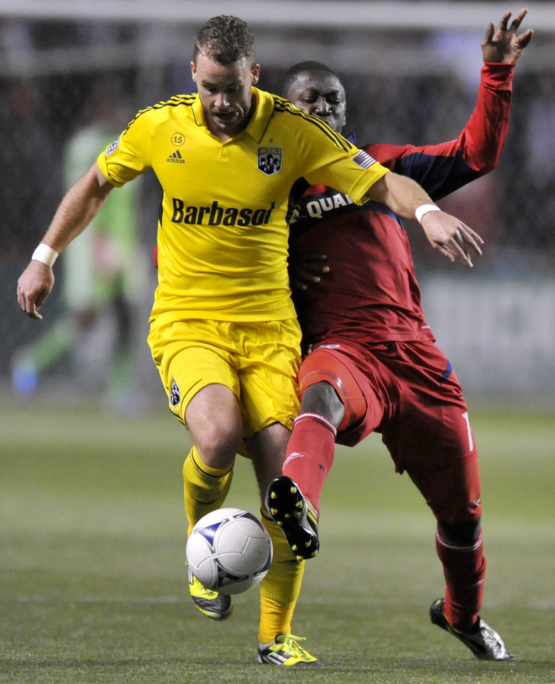 Photo -   Columbus Crew's Josh Williams left, battles Chicago Fire's Patrick Nyarko right, for the ball during the first half of an MLS soccer match in Bridgeview, Ill., Saturday, Sept. 22, 2012. (AP Photo/Paul Beaty)