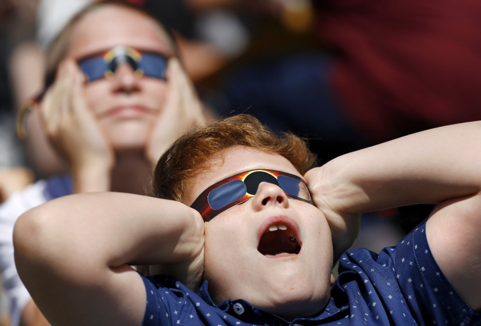 Photo - Joelston Miller, foreground, and Jordan Oakley, both fourth graders, react to seeing the moon pass in front of the sun.  The entire student body, faculty and some parents gathered in a field on the north side of  James Griffith Intermediate School to view the solar eclipse Monday afternoon, Aug. 21, 2017.  Special glasses with very dark lenses were purchased to allow teachers and students to safely view the celestial event. Children were served  Moon Pies as a snack to enjoy while viewing the eclipse. Photo by Jim Beckel, The Oklahoman