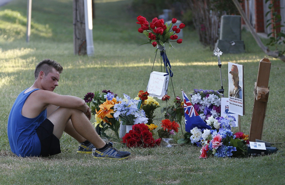 Twenty-three year old Aaron Boyer, who lives nearby, sits by the memorial for slain Australian Christopher Lane while out for a run in Duncan, Okla., Tuesday, Aug. 20, 2013. Lane, who was on a baseball scholarship at East Central University in Ada, Okla., was in Duncan, Okla., visiting his girlfriend, when he was shot and killed Friday, Aug. 16, 2013.(AP Photo/Sue Ogrocki) ORG XMIT: OKSO118