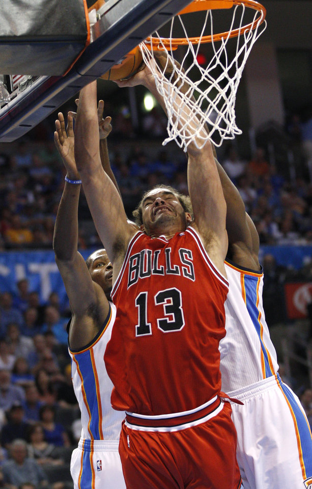 Photo -   Chicago Bulls center Joakim Noah (13) shoots in front of Oklahoma City Thunder forward Kevin Durant, left, and forward Serge Ibaka, right, of the Republic of Congo, in the second quarter of an NBA basketball game in Oklahoma City, Sunday, April 1, 2012. (AP Photo/Sue Ogrocki)