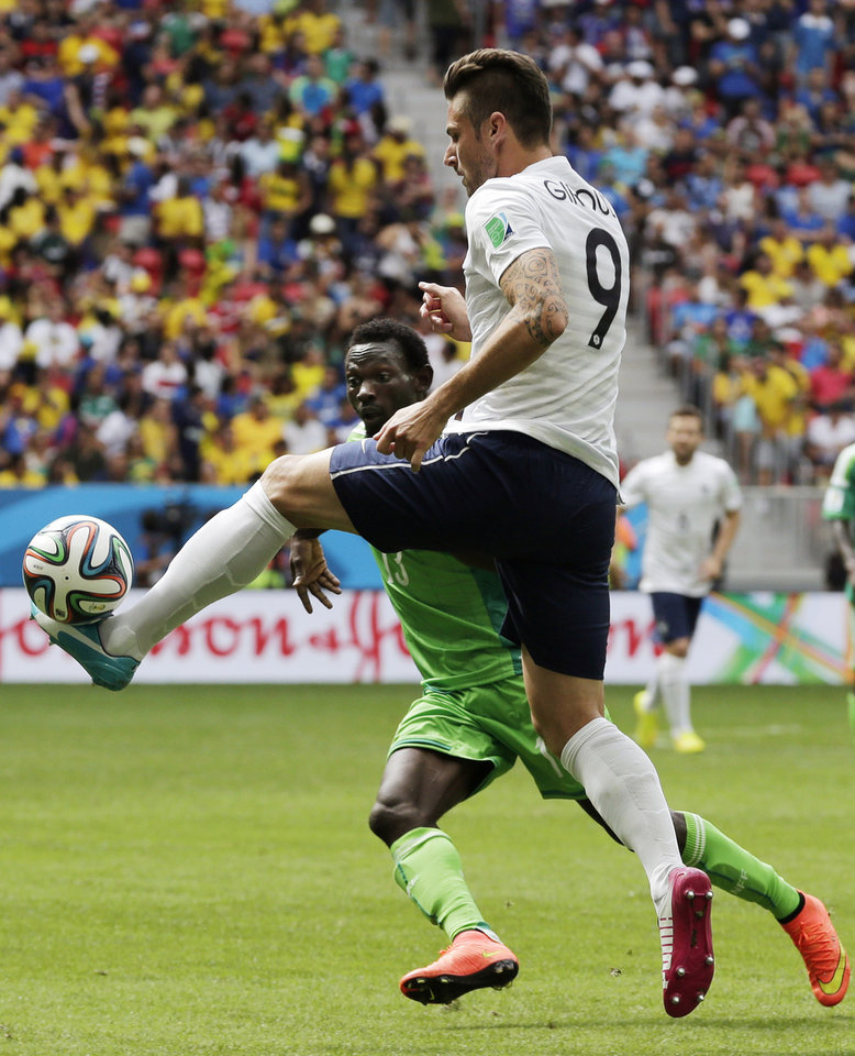 Photo - France's Olivier Giroud, right, clears the ball ahead of Nigeria's Juwon Oshaniwa during the World Cup round of 16 soccer match between France and Nigeria at the Estadio Nacional in Brasilia, Brazil, Monday, June 30, 2014. (AP Photo/Petr David Josek)