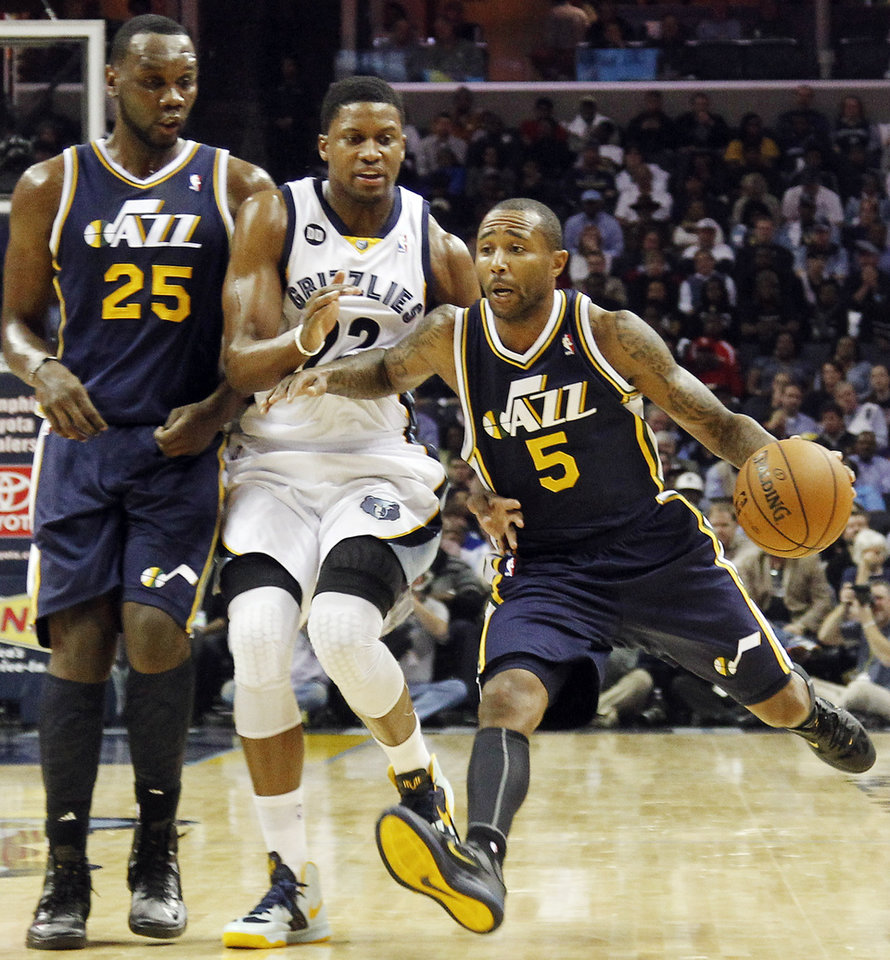 Utah Jazz guard Mo Williams (5) drives on Memphis Grizzlies forward Rudy Gay (22) as Jazz center Al Jefferson (25) watches in the first half of an NBA basketball game, Monday, Nov. 5, 2012, in Memphis, Tenn. (AP Photo/Lance Murphey)