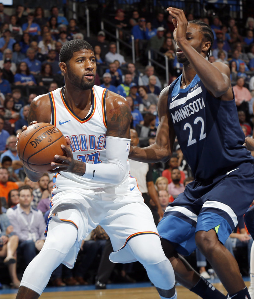 Photo - Oklahoma City's Paul George (13) keeps the ball away from Minnesota's Andrew Wiggins (22) during an NBA basketball game between the Oklahoma City Thunder and the Minnesota Timberwolves at Chesapeake Energy Arena in Oklahoma City, Sunday, Oct. 22, 2017. Photo by Nate Billings, The Oklahoman
