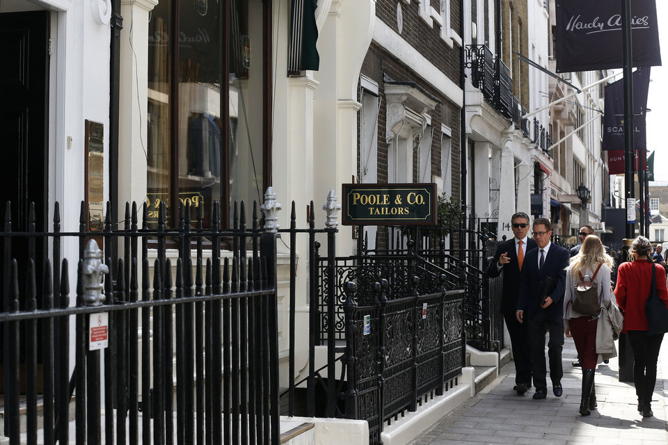Photo - In this photo taken Friday, June 6, 2014, people walk by Henry Poole & Co tailor, the first shop to set up in Savile Row in 1846, on Savile Row in London. In the world of women's fashion, London often seems to play second fiddle to other style capitals: It lacks the allure of Paris's haute couture, or the polish of Milan's luxury labels. But it's a whole different story when it comes to dressing men. Steeped in a rich history of tailoring for kings, army generals and the world's wealthiest men, London is now marketed as the home of men's fashion - the original birthplace of the tuxedo jacket, the bowler hat and the three-piece suit, among other classic items. When trendy designers like Alexander McQueen and Burberry kick off the new season's menswear shows in the British capital Sunday, the catwalks will be staged just blocks away from elite tailoring houses that have been perfecting their craft for over a century. Savile Row, a street lined with more than a dozen tailors and a living museum of the English love affair with luxury menswear, has a long-standing tradition closely tied to a history in royal dress, military uniforms and gentry sports like horseback riding and hunting. (AP Photo/Sang Tan)
