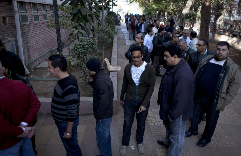 Photo - Egyptians queue to vote outside a gymnasium hall that is used as a polling station during the second round of a referendum on a disputed constitution drafted by Islamist supporters of president Mohammed Morsi, in Giza, Egypt, Saturday, Dec. 22, 2012. (AP Photo/Nasser Nasser)