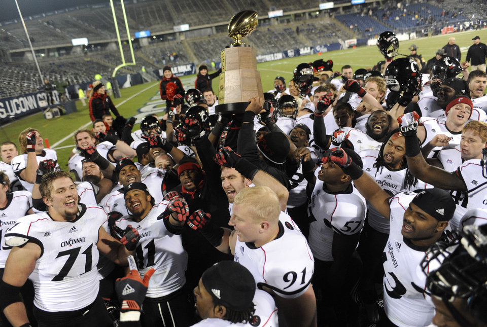 Photo - Cincinnati holds up the Big East Championship trophy at the end of an NCAA college football game against Connecticut at Rentschler Field in East Hartford, Conn., Saturday, Dec. 1, 2012. Cincinnati is sharing the title along with Rutgers, Syracuse and Louisville. Cincinnati defeated Connecticut 34-17. (AP Photo/Jessica Hill)