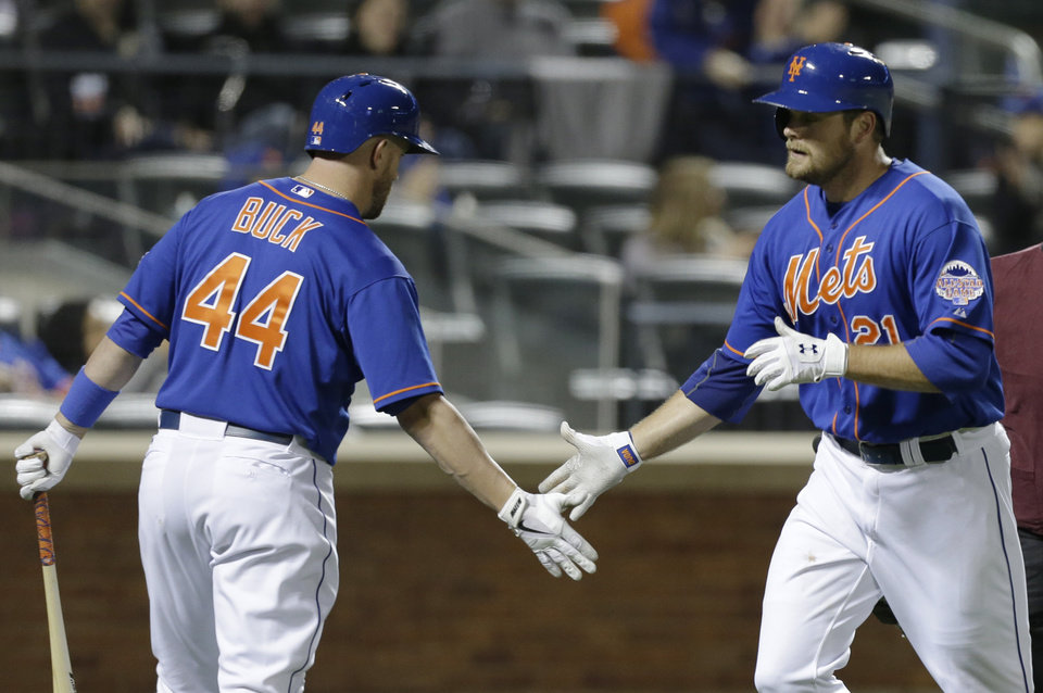 New York Mets' John Buck (44) greets teammate Lucas Duda (21) after Duda hit a fourth-inning solo home run off Atlanta Braves starting pitcher Julio Teheran in a baseball game at Citi Field in New York, Sunday, May 26, 2013. (AP Photo/Kathy Willens)