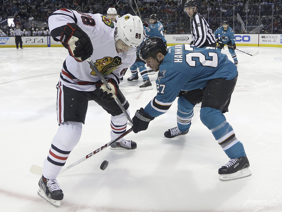 Photo - Chicago Blackhawks right wing Patrick Kane (88) tangle up for the puck against San Jose Sharks defenseman Scott Hannan (27) during the second period of an NHL hockey game in San Jose, Calif., Saturday, Feb. 1, 2014. (AP Photo/Tony Avelar)