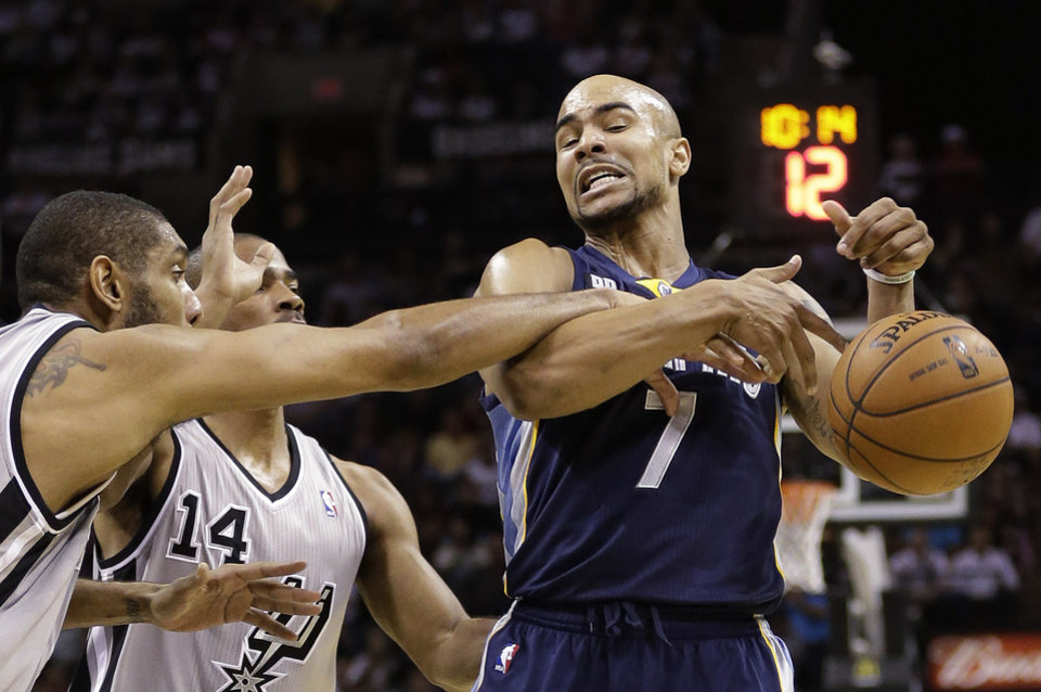 Memphis Grizzlies' Jerryd Bayless (7) is fouled by San Antonio Spurs' Tim Duncan, left, during the first quarter of an NBA basketball game, Saturday, Dec. 1, 2012, in San Antonio. Spurs' Gary Neal (14) helps defend on the play. (AP Photo/Eric Gay)