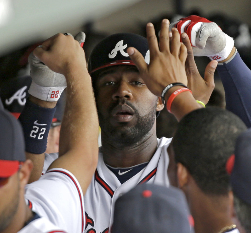 Photo - Atlanta Braves' Jason Heyward is congratulated in the dugout after hitting a home run against the Miami Marlins during the fourth inning of an exhibition spring training baseball game Monday, Feb. 25, 2013, in Kissimmee, Fla. (AP Photo/David J. Phillip)