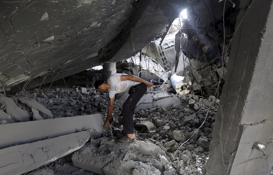 Photo - A Palestinian searches the ruins of the Al-Tawfeeq mosque after it was hit by an Israeli missile strike in the Nuseirat refugee camp, central Gaza Strip, Saturday, July 12, 2014.  Palestinian officials said Israeli airstrikes in Gaza hit a mosque and a center for the disabled where two women were killed Saturday, raising the Palestinian death toll to more than 120, in an offensive that showed no signs of slowing down. (AP Photo/Hatem Moussa)