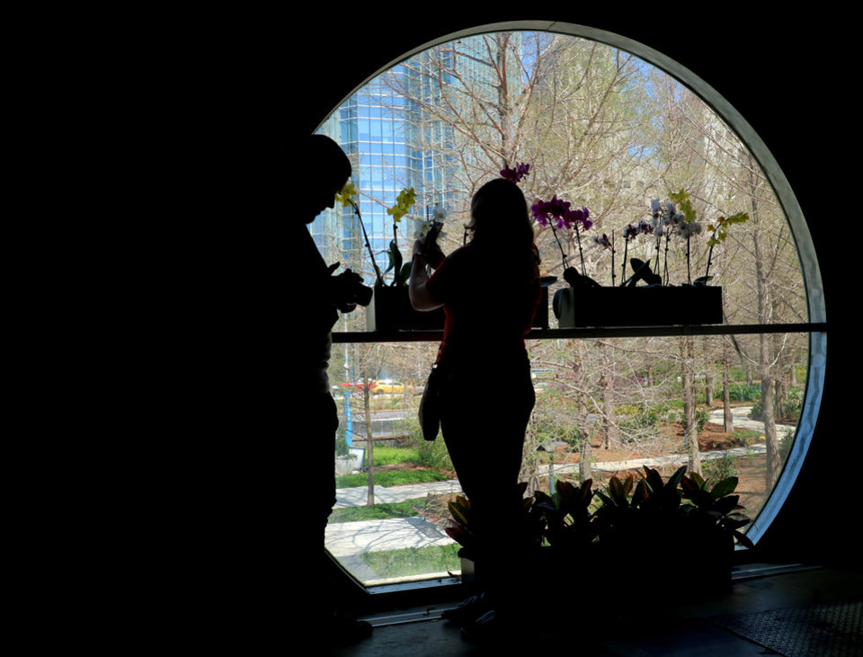 Photo - Michael Chiri and his wife, Lauren take photos out the window in the north end during the anniversary of the Crystal Bridge at the Myriad Botanical Gardens in downtown Oklahoma City, March 25, 2016. The Crystal Bridge opened on this date 28 years ago and as part of the anniversary, admission was free today. Photo by Doug Hoke, The Oklahoman