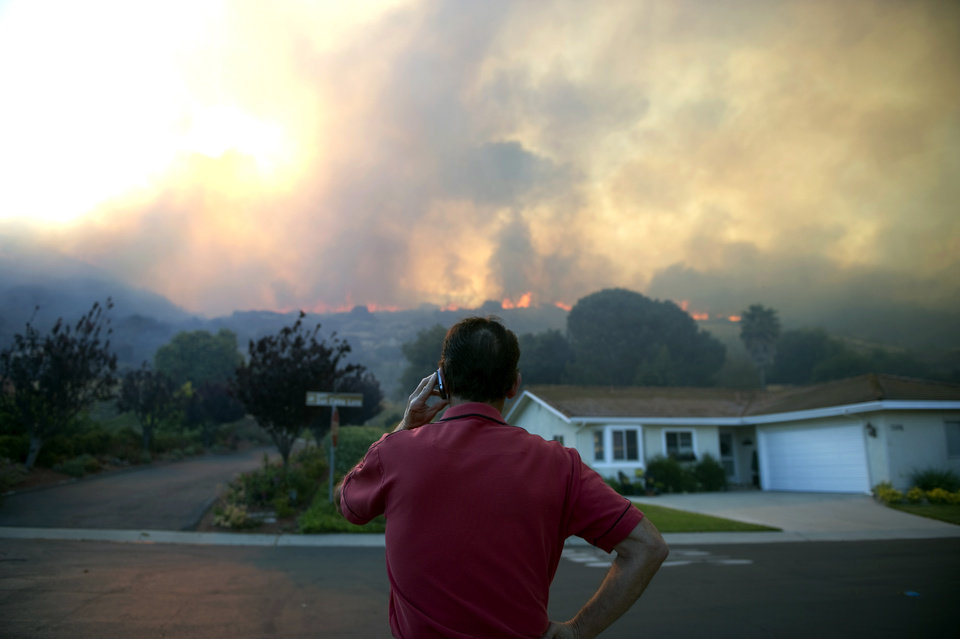 Reuben Ruiz makes a phone call as he watches the flames from a brush fire in Camarillo, Calif., Thursday, May 2, 2013. (AP Photo/The Ventura County Star, Troy Harvey) LOS ANGELES TIMES OUT, LOS ANGELES DAILY NEWS OUT