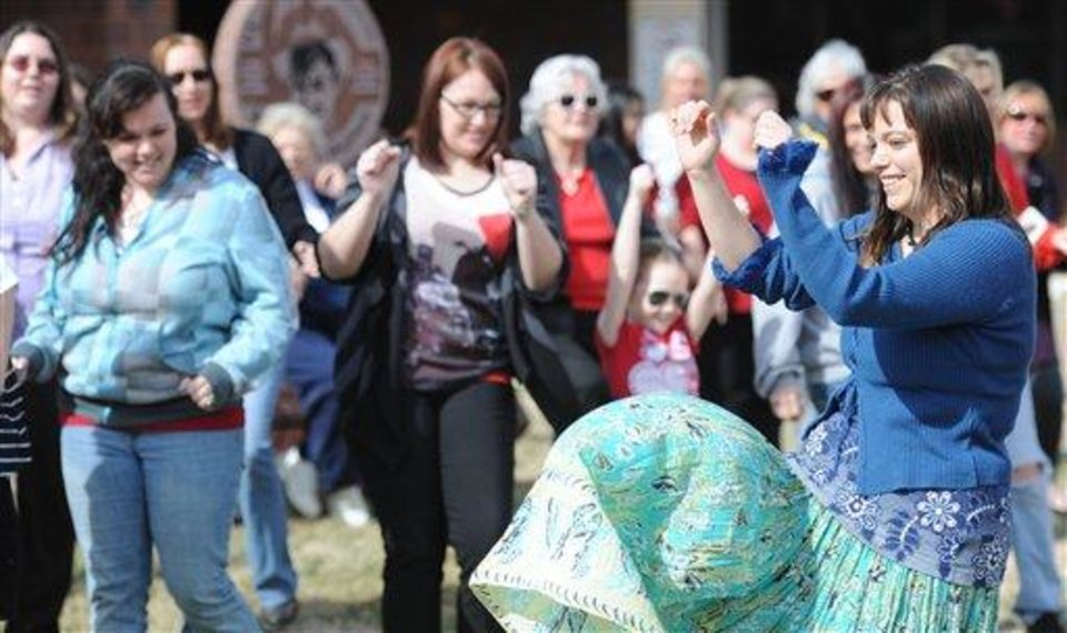 Photo - Shelli Jones, of Joplin, Mo., right, leads a group of women in a dance for the international One Billion Rising event Thursday afternoon, Feb. 14, 2013. This event is among thousands of taking place in 205 countries Thursday as part of One Billion Rising, an international call led by Eve Ensler's V-Day organization to end violence against women and girls. (AP Photo/The Joplin Globe, T. Rob Brown)
