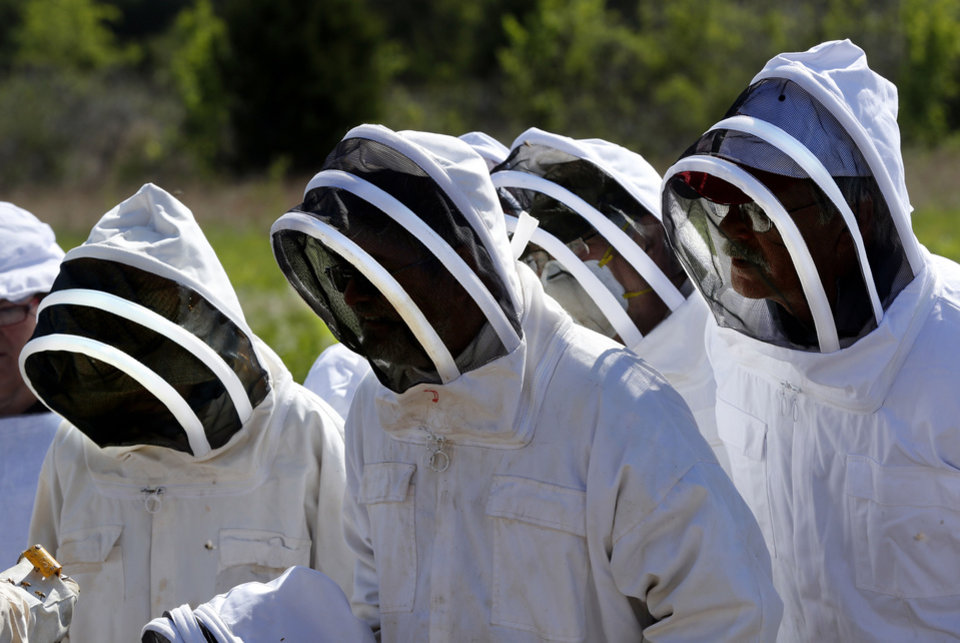 Participants wear bee suits as Brian Royal demonstrates beekeeping techniques at his home based business at Norman.  <strong>STEVE SISNEY - THE OKLAHOMAN</strong>