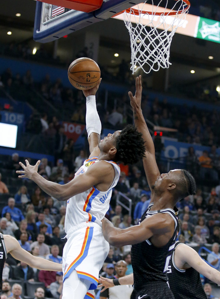 Photo - Oklahoma City's Shai Gilgeous-Alexander goes up for a basket as Sacramento's Harry Giles III (20) defends during the NBA basketball game between the Oklahoma City Thunder and the Sacramento Kings at the Chesapeake Energy arena in Oklahoma City,  Thursday, Feb. 27, 2020.  [Sarah Phipps/The Oklahoman]