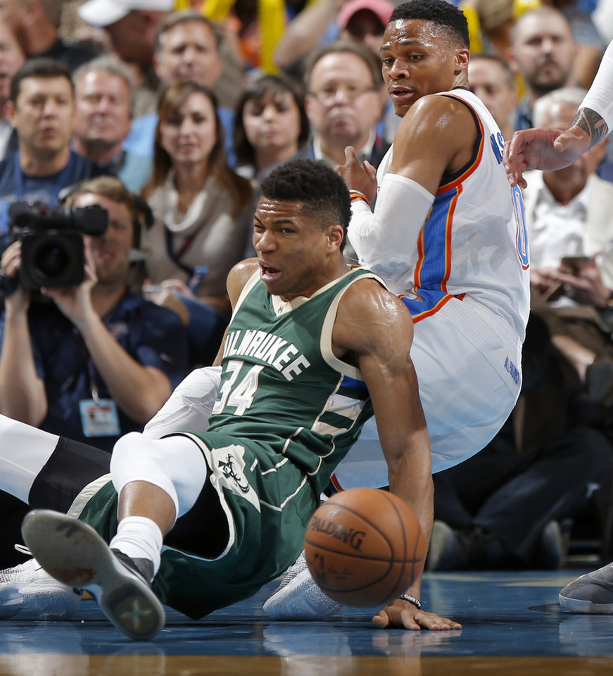 Photo - Oklahoma City's Russell Westbrook (0) falls down beside Milwaukee's Giannis Antetokounmpo (34) during an NBA basketball game between the Oklahoma City Thunder and the Milwaukee Bucks at Chesapeake Energy Arena in Oklahoma City, Tuesday, April 4, 2017. Photo by Bryan Terry, The Oklahoman