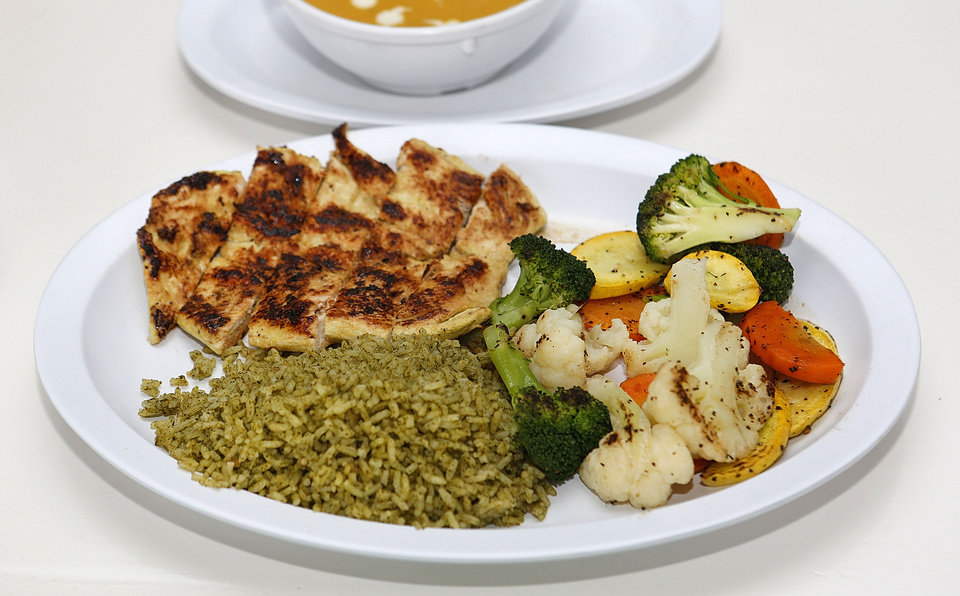 Photo - Chicken with vegetables and rice at Green and Grilled in Oklahoma City. Photo By Steve Gooch, The Oklahoman  Steve Gooch - The Oklahoman