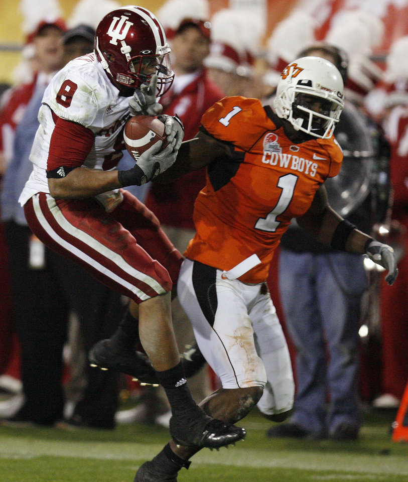 Photo - Indiana's Nick Polk (8) intercepts a ball intended for Oklahoma State's Dez Bryant (1) in the first half during the Insight Bowl college football game between Oklahoma State University (OSU) and the Indiana University Hoosiers (IU) at Sun Devil Stadium on Monday, Dec. 31, 2007, in Tempe, Ariz. 