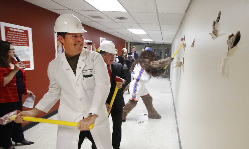 Photo - Dr. Cameron Mantor, chief medical officer for The Children's Hospital at OU Medical Center, left, and Lance Benham, a member of the advisory committee for Ronald McDonald House Charities of Oklahoma City, break down a wall with Rumble the Bison Thursday during the announcement of a second Ronald McDonald House being built in Oklahoma City.  Photo By Steve Gooch, The Oklahoman   Steve Gooch