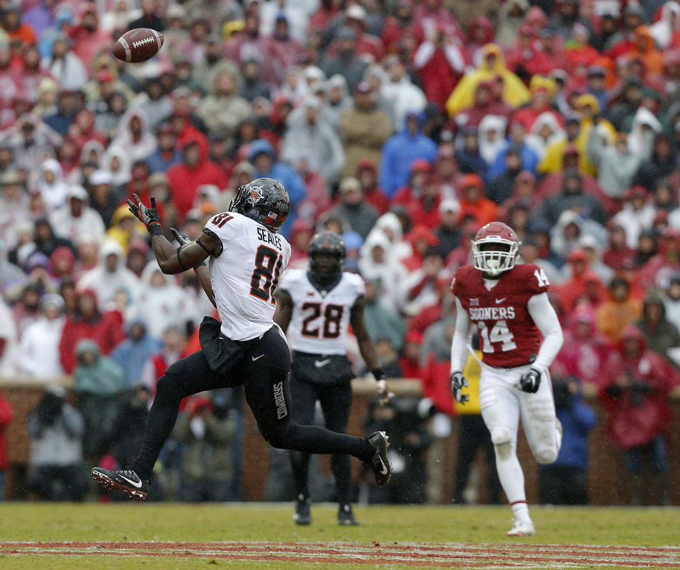 Photo - Oklahoma State's Jhajuan Seales (81) makes a catch in front of Oklahoma's Emmanuel Beal (14) in the third quarter during the Bedlam college football game between the Oklahoma Sooners (OU) and the Oklahoma State Cowboys (OSU) at Gaylord Family - Oklahoma Memorial Stadium in Norman, Okla., Saturday, Dec. 3, 2016. OU won 38-20. Photo by Sarah Phipps, The Oklahoman
