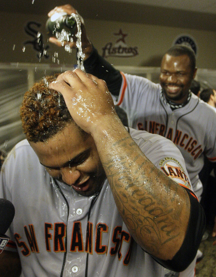 Photo -   San Francisco Giants' Pablo Sandoval has champagne poured over him while being interviewed in the clubhouse after the Giants defeated the Cincinnati Reds 6-4 in Game 5 of the National League division baseball series, Thursday, Oct. 11, 2012, in Cincinnati. The Giants won the final three games, all in Cincinnati, and advanced to the NL championship series. (AP Photo/David Kohl)