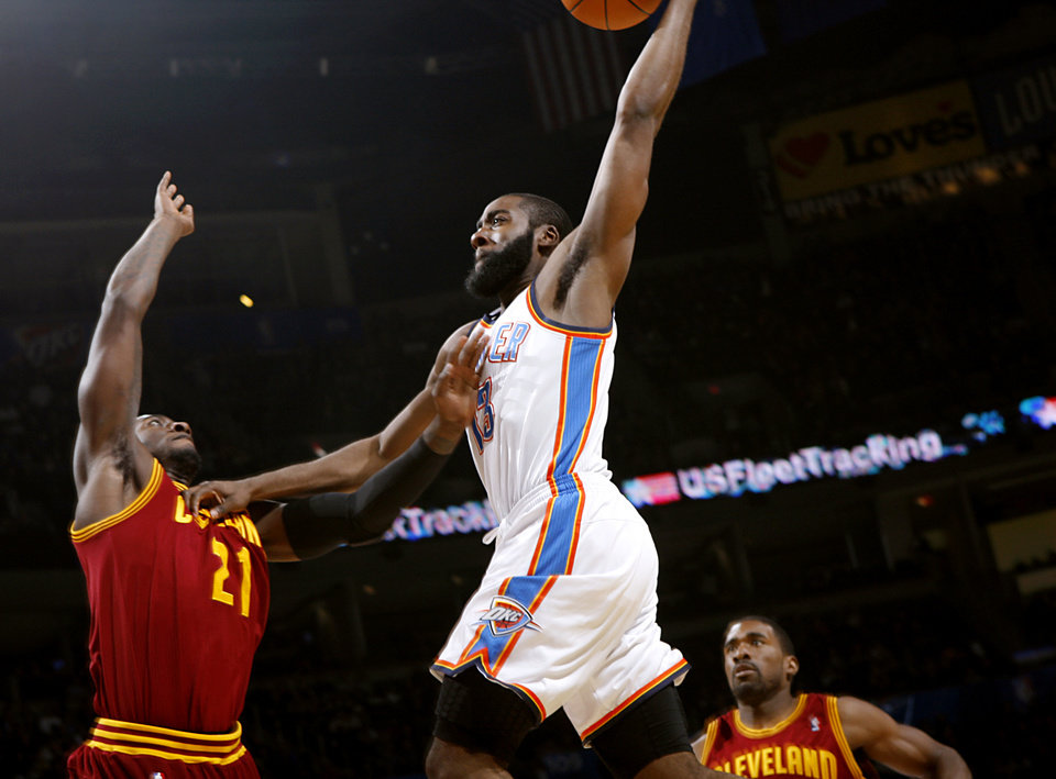 Photo - Oklahoma City's James Harden slams the ball over Cleveland's J.J. Hickson (left) during the first half of their NBA basketball game at the OKC Arena in Oklahoma City on Sunday, Dec. 12, 2010. Photo by John Clanton, The Oklahoman