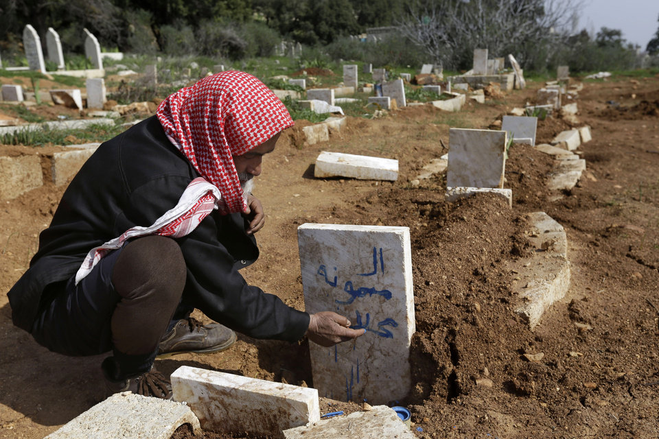 Photo - A Syrian villager, Abu Ibrahim, 73, writes the name of his granddaughter on her grave who was killed from an airstrike by Syrian government forces, at Jabal al-Zaweya village of Sarja, in Idlib, Syria, Sunday, Feb. 24, 2013. Syrian rebels used captured tanks to launch a fresh offensive on a government complex housing a police academy near Aleppo and clashed with government troops protecting the strategic installation on Sunday. (AP Photo/Hussein Malla)